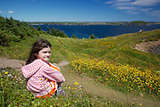 Young girl taking a break on the Skerwink Trail in Newfoundland.