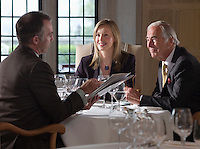 Three business people sitting at restaurant table one man holding documents