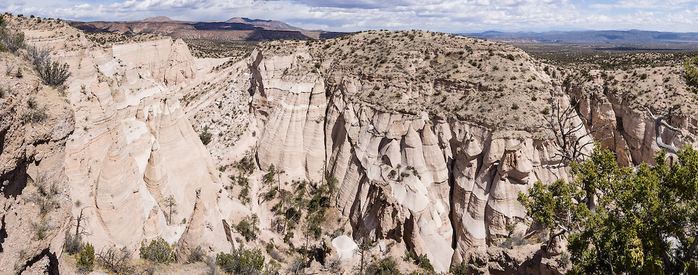 """Hoodoos panorama. See fantastic hoodoos and a great slot canyon in Kasha-Katuwe Tent Rocks National Monument, in New Mexico, USA. Hike the easy Cave Loop Trail plus Slot Canyon Trail side trip (3 miles round trip), 40 miles southwest of Santa Fe, on the Pajarito Plateau. Distinctive cone-shaped caprocks protect soft pumice and tuff beneath. Geologically, the Tent Rocks are made of Peralta Tuff, formed from volcanic ash, pumice, and pyroclastic debris deposited over 1000 feet thick from the Jemez Volcanic Field, 7 million years ago. Kasha-Katuwe means """"white cliffs"""" in the Pueblo language Keresan. This panorama was stitched from 8 overlapping photos."""