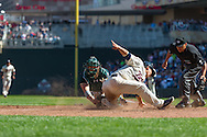 Kurt Suzuki #8 of the Minnesota Twins slides safely into home plate for the game-tying run in the 9th inning ahead of the tag by Derek Norris #36 of the Oakland Athletics on April 9, 2014 at Target Field in Minneapolis, Minnesota.  The Athletics defeated the Twins 7 to 4.  Photo by Ben Krause