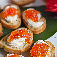 Orange pepper jelly on herbed cream cheese on rounds of toast.