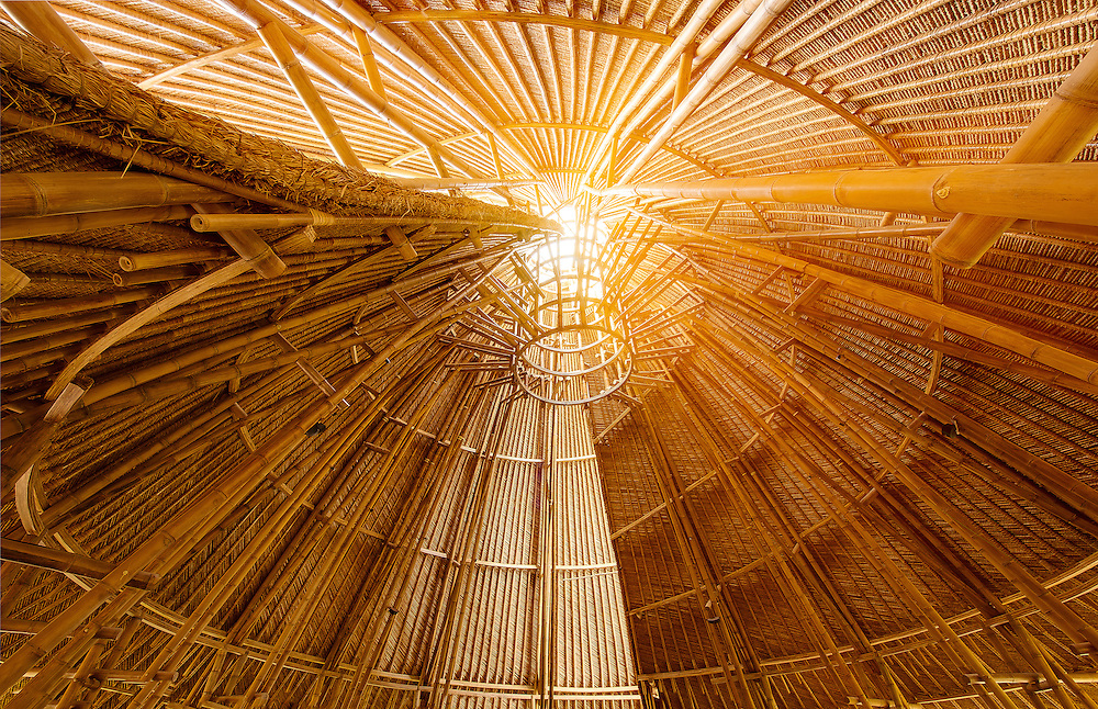 """The interior of the Mandala Agung tower reveals bamboo arced into a graceful double spiral. The realization of  """"sacred geometry"""" was a guiding principal in the construction Fivelements Healing Center. The open architecture admits soft natural light and a cooling breeze."""