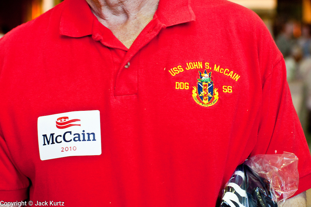 Aug. 23, PHOENIX, AZ: A McCain supporter wears a McCain sticker and a golf shirt from the US Navy ship USS John McCain at a McCain campaign rally in Phoenix Monday. The USS John McCain is named after the Senator's father and grandfather, who were both Admirals in the Navy. It is not named after the Senator. US Sen. John McCain held the final of his primary election campaign at his campaign offices in Phoenix Monday. McCain, Arizona's senior Republican US Senator, is facing former Congressman JD Hayworth in the primary, Tuesday, Aug. 24. McCain has outspent Hayworth by a considerable margin and is expected to win.   Photo by Jack Kurtz