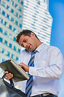 Portrait of handsome mature businessman talking on smartphone checking appointment on digital tablet