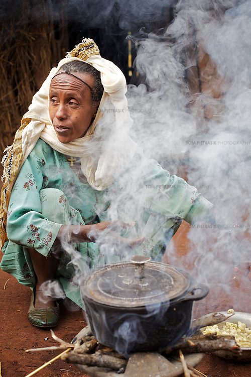 Belaynesh cooks breakfast for her neice and herself outside their home in the village of Amba Zetegn. <br /> <br /> Belaynesh Hussen (age 50) lives with her niece Tsehaynesh Bistegn, age 10, in a thatched house in Amba Zetegn, 20km from Assosa town. She farms sorghum, maize, teff and soya, all sold through the local farmers co-operative society of which she has been a part for the past three years. This village co-op is affiliated to the Assosa Farmers Multipurpose Cooperative Union.<br /> <br /> Growing oil seeds presents challenges for the famers of Assosa in western Ethiopia. Many of the most vulnerable are forced to sell to when they cannot be guaranteed a good price for their product. Farms are often located in isolated areas which entails huge amounts of time and effort simply getting seeds to market. Many farmers do not have the resources to properly invest in their land and are tied into exploitative loan arrangements with brokers that deny them the chance to take proper control of their farms. And, as with other agricultural products, it is those agents that process the seeds into oil that secure the greatest profit, very little of which trickles down to benefit the farmer.<br /> <br /> In response to these pressures, twenty farming cooperatives have formed the Assosa Farmers Multipurpose Cooperative Union. By working together, individual farmers are able to pool their resources and squeeze out exploitative agents and brokers. The Union has sufficient capital that it can afford to wait for prices to reach a level at which it is profitable to sell seeds to market. The Union provides loans to constituent members together with training and advice to help farmers make better use of their land. And by collectively hiring vehicles through the Union, farmers need not spend so much time ferrying their produce to market. <br /> <br /> All these measures benefit farmers and have now provided the Assosa Farmers Multipurpose Cooperative Union the confidence to establis