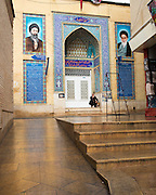 On the wall of a mosque are the portraits of Ayatollahs Khamenei (left) and Khomeyni (right), all present in Iran.