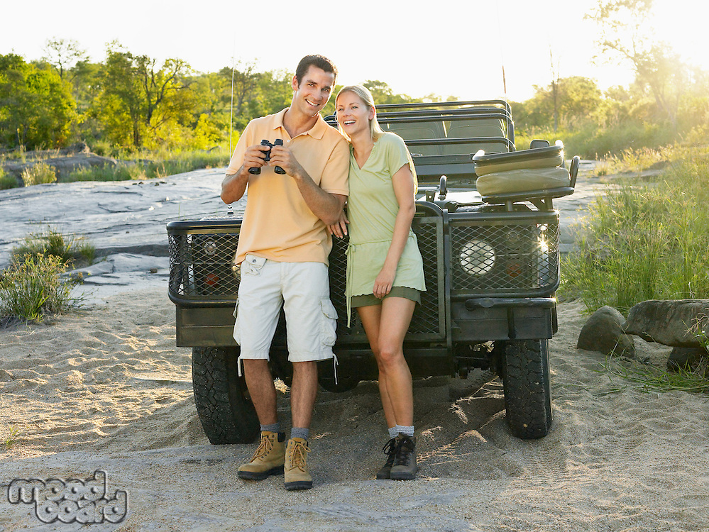 Couple standing by jeep looking at view man holding binoculars smiling
