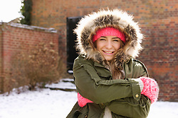 Smiling Teenage Girl Wearing Parka Hugging Herself Outdoors