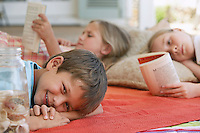 Three children (5-6 7-910-12) lying on blanket outdoors focus on boy