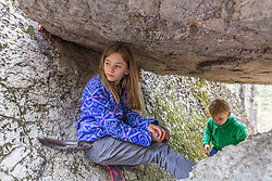 A girl and boy play in a small cave formed by large glacial erratics in the Stonehouse Forest in Barrington, New Hampshire.