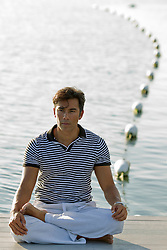 Asian American Man sitting on a dock by the bay