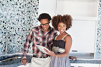 Portrait of young African American couple with color swatches in new kitchen