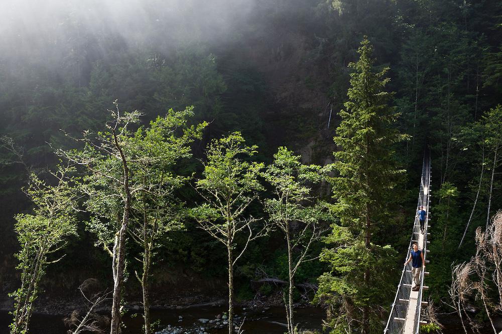 Henry (front) and Zach Podell-Eberhardt cross the suspension footbridge across Logan Creek, West Coast Trail, British Columbia, Canada.