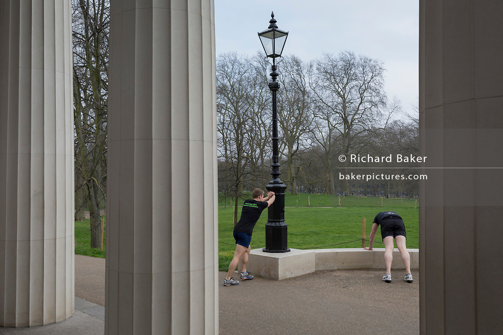 Seen between the columns of the Bomber Command War memorial in Green Park, two joggers stretch their legs after their run, on 16th March 2017, in London, England.
