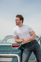 hot muscular man leaning on a car from the 1960's