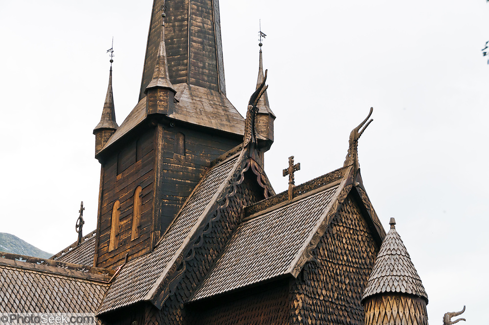 "Turret towers and dragon head design motif. Built in 1170, Lom Stave Church (stavkirke or stavkyrkje) was rebuilt into a cruciform, triple-nave church in 1663 and restored in 1933 and 1973. Visit this wooden Norman-style church in the town of Lom, in Gudbrandsdal, Oppland county, Norway. ""Staves"" are upright logs that support the central room framework."