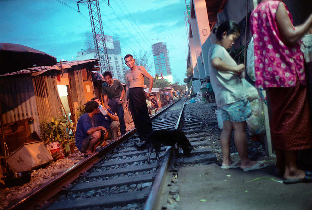 Slum dwellers living by the railway tracks. Many come from the countryside and have settled here to look for better job prospects in the big city.