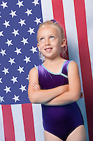 Happy young female gymnast with arms crossed standing in front of American flag