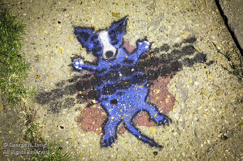 graffiti on sidewalk depicting artist George Rodrigue's 'Blue Dog' being run over by a car; tire tracks and blood