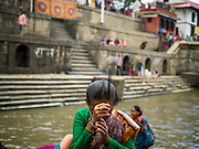03 AUGUST 2015 - KATHMANDU, NEPAL:      A Hindu woman prays on the banks of the Bagmati River at Pashupatinath, a complex of important Hindu temples in Kathmandu. The Bagmati River runs through the complex. It is Nepal's most holy river, and this stretch of the river is like Varanasi in India. The river bank is lined with cremation ghats. Many Hindus, from both Nepal and India, make pilgrimages to Pashupatinath.   PHOTO BY JACK KURTZ