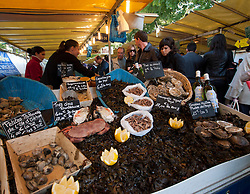 Shellfish for sale at seafood stall in traditional market at Bastille in Paris France