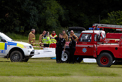© Licensed to London News Pictures.  01/07/2012. Bedford, UK. Emergency vehicles surround the scene of a light aircraft crash at Old Warden Aerodrome, near Biggleswade. The rare 1920s de Havilland DH 53 crashed while taking part in a local air display. The pilot, thought to be Trevor Roche, died in the accident. Photo credit :  Cliff Hide/LNP
