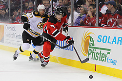 Jan 19; Newark, NJ, USA; New Jersey Devils defenseman Adam Larsson (5) skates with the puck while being defended by Boston Bruins center Chris Kelly (23) during the first period at the Prudential Center.