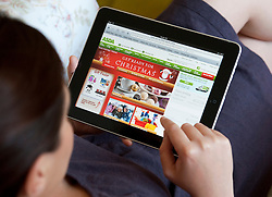 Woman shopping for Christmas at online Asda supermarket store using an iPad tablet computer