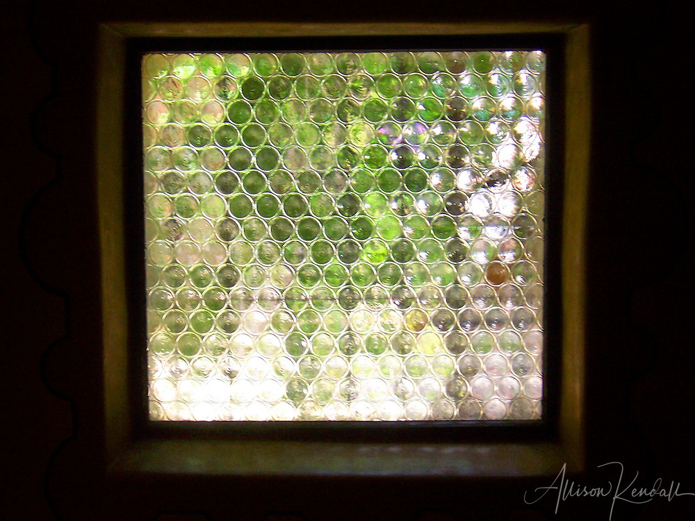 A textured window at Carmel Mission creates an abstract view of the gardens