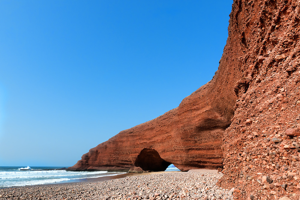 Natural sea-worn rock archways against clear blue sky at Legzira beach, Morocco.