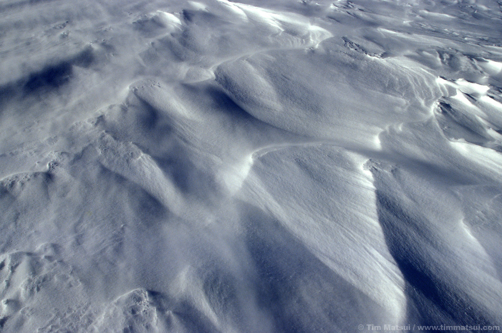 Spindrift blows over windswept snow.