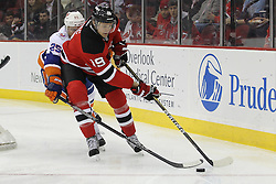 Apr 3; Newark, NJ, USA; New Jersey Devils center Travis Zajac (19) skates with the puck while being defended by New York Islanders right wing Nino Niederreiter (25) during the first period at the Prudential Center.