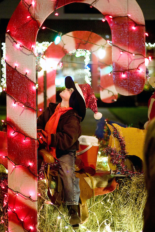 JEROME A. POLLOS/Press..Garek Pennington, 7, inspects the lighting on the candy cane decorated float for the Kootenai County Saddle Club.