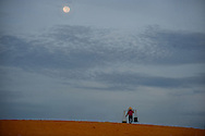 A woman makes her way over a sand dune to sell meals to the locals.