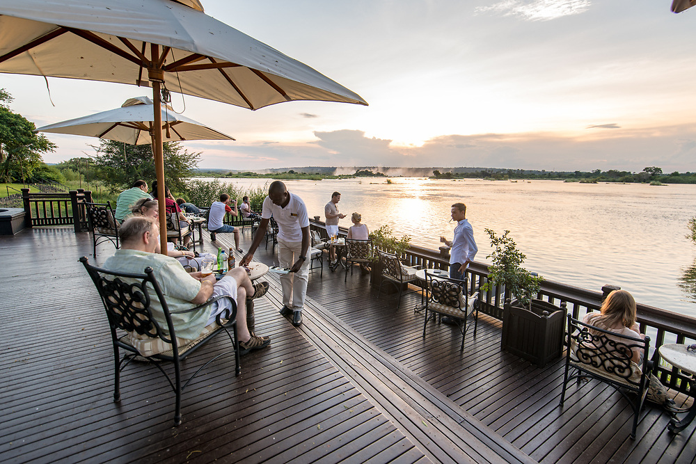 A group of hotel guests of the Royal Livingstone Hotel sit on the sundeck and watch the sun set over the Zambezi River Livingstone, Zambia