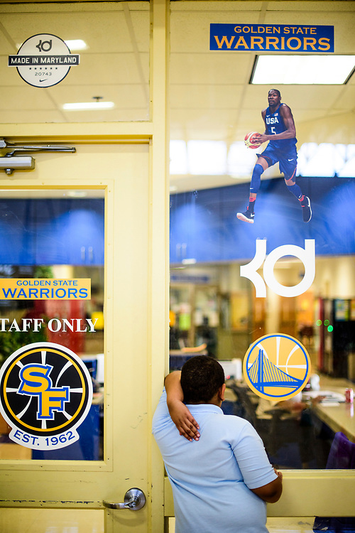 Capitol Heights, Maryland - March 29, 2017: A student stands next to decals of NBA super star Kevin Durant at Seat Pleasant Activity Center March 29, 2017.<br /> <br /> NBA super star Kevin Durant has donated a substantial amount of money to help renovate the Seat Pleasant Activity Center where he learned to play basketball. Durant's AAU coach and mentor Charles &quot;Chuckie&quot; Craig, who worked at the Activity Center, was gunned down in May 2005 at the age of 35. Durant wears #35 in Craig's honor.<br /> <br /> <br /> NBA Superstar Kevin Durant's jersey number &quot;35&quot; is a tribute to his rec. league coach and mentor Charles &quot;Chuckie&quot; Craig, who was gunned down in at a night club in Laurel, Md., in 2005 when he was 35 years old. <br /> <br /> CREDIT: Matt Roth for The New York Times<br /> Assignment ID: 30204524A