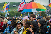 The rain comes down again and an umbrella in support of Pride goes up. Ellie Goulding plays the Pyramid Stage - The 2016 Glastonbury Festival, Worthy Farm, Glastonbury.
