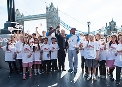 Image ©Licensed to i-Images Picture Agency. 06/06/2014. London, United Kingdom. Mayor of London Boris Johnson holds the Commonwealth Games Queen\'s Baton Relay with Michael Pusey (left), World and Commonwealth champion Christine Ohuruogu MBE (back), Faramolu Johnson (right) and local schoolchildren to the capital as part of the England led of a journey that will see it travel 190,000 kilometres over 288 days. City Hall, The Queen\'s Walk. Picture by Daniel Leal-Olivas / i-Images