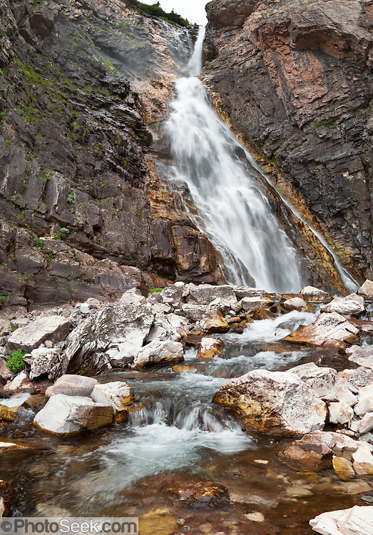 "Apikuni Creek tumbles over Apikuni Falls in Glacier National Park, Montana, USA. Hike 1.6 miles round trip ascending 880 feet, starting from Grinnel Glacier Exhibit 1.1 miles east of the Many Glacier Hotel. Since 1932, Canada and USA have shared Waterton-Glacier International Peace Park, which UNESCO declared a World Heritage Site (1995) containing two Biosphere Reserves (1976). Rocks in the park are primarily sedimentary layers deposited in shallow seas over 1.6 billion to 800 million years ago. During the tectonic formation of the Rocky Mountains 170 million years ago, the Lewis Overthrust displaced these old rocks over newer Cretaceous age rocks. Glaciers carved spectacular U-shaped valleys and pyramidal peaks as recently as the Last Glacial Maximum (the last ""Ice Age"" 25,000 to 13,000 years ago). Of the 150 glaciers existing in the mid 1800s, only 25 active glaciers remain in the park as of 2010, and all may disappear by 2020, say climate scientists."