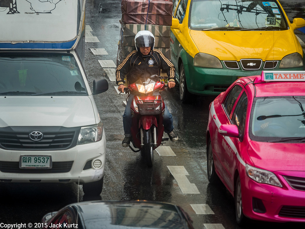 "16 SEPTEMBER 2015 - BANGKOK, THAILAND:  A motorcyclist rides down Phaya Thai Street in the rain in Bangkok. The remnants of tropical storm ""Vamco"" hit Bangkok Wednesday. Storm, downgraded to a tropical depression, brought bands of rain to central Thailand, including Bangkok. The Thai Meteorological Department said the storm would help alleviate the drought that has gripped Thailand since late last year.    PHOTO BY JACK KURTZ"