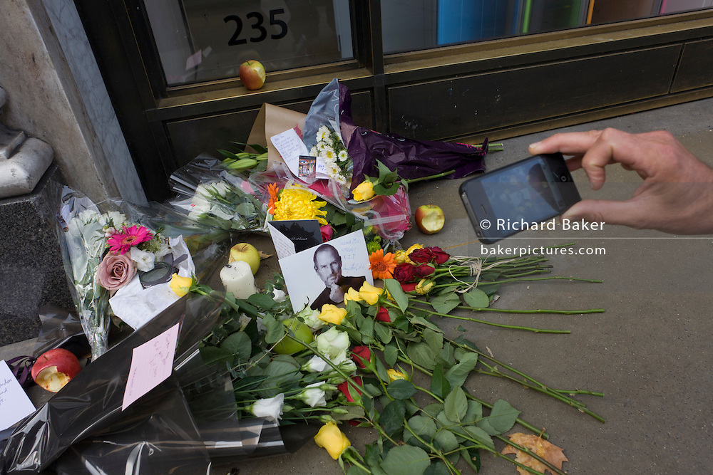 Fans use smartphones to photograph the makeshift shrine, where Londoners commemorate Apple's creator Steve Jobs the morning after hearing of his death overnight from pancreatic cancer  at the age of 56 on the 6th Oct 2011. This Apple Store in the capital's Regent's Street was the first to be built in Europe and serves as a flagship outlet for the stylish brand of computer accessories that were largely the brainchild of Jobs who started the company as a student in 1977.