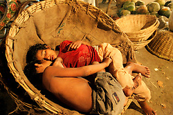 BANGLADESH DHAKA KAWRAN BAZAAR 1MARB05 - Two homeless children sleep in an empty basket at Kawran Bazaar vegetable market. The Bazaar has been in the Tejgaon area for at least 30 years and is one of the largest markets in Dhaka city...jre/Photo by Jiri Rezac ..© Jiri Rezac 2005..Contact: +44 (0) 7050 110 417.Mobile:  +44 (0) 7801 337 683.Office:  +44 (0) 20 8968 9635..Email:   jiri@jirirezac.com.Web:    www.jirirezac.com..© All images Jiri Rezac 2005- All rights reserved.