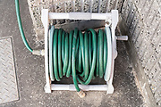 rolled up green garden water hose