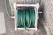 rolled up green garden water hose