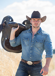 good looking cowboy with a saddle outdoors in a field