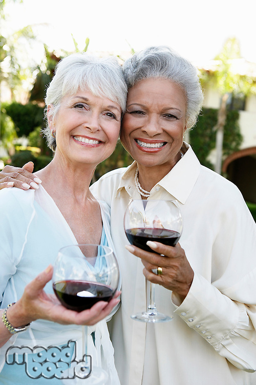 Middle-aged Friends standing outside Drinking Wine from wineglasses