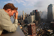 Brian Boyd, who has just been let into his home at 41 River Terrace, looks out onto the World Trade Center site for the first time from the view of his roof in Manhattan, NY, September 21, 2001. Photo by Jennifer S. Altman