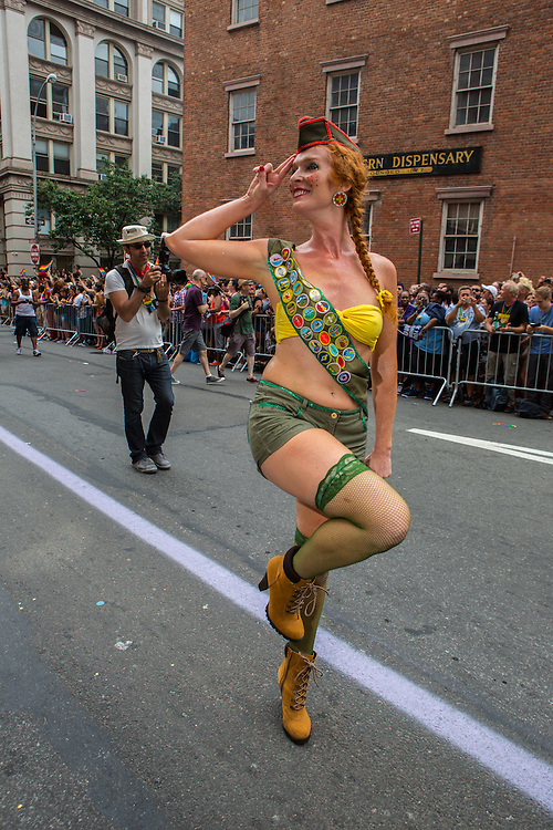 A woman wearing a Boy Scout-like merit badge sash and green fishnet stockings gives a mock salute to the crowd, satirizing the American Boy Scouts' atitude towards gay scouts and scout leaders.