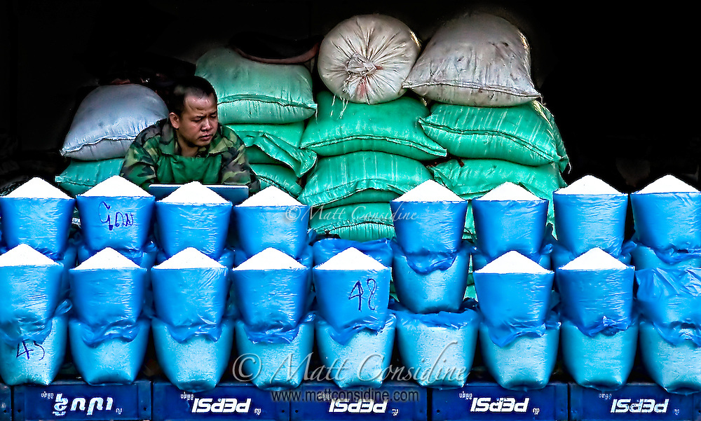 Rice Vendor waiting for customers and maybe checking the prices of rice futures on the net.<br /> (Photo by Matt Considine - Images of Asia Collection)