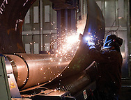 A worker welds a section of a wind turbine tower at Trinity Structural Towers in Newton, Iowa on February 12, 2010.